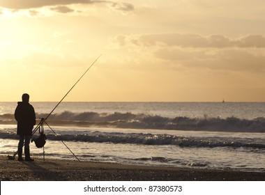 Angler on deserted beach at sunset