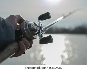 Angler on the river with close up baitcasting reel in hilights