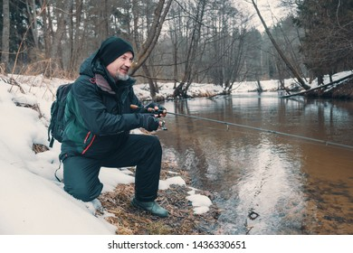 Angler with a rod on the river bank. Fishing for trout. Winter spinning.