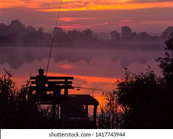 Angler seating on the wooden pier by the lake at down holding fishing rod. Silhouette landscape with beautiful summer sunlight.