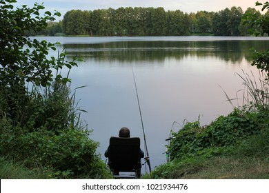 angler sitting on a chair for fishing in a lake
