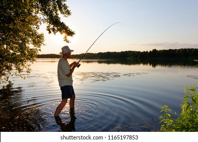 Angler standing in a lake and catching the fish during sunset