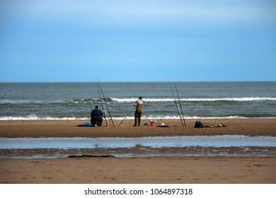 Anglers are fishing on the seashore. St Cyrus, Aberdeenshire, Scotland, UK.