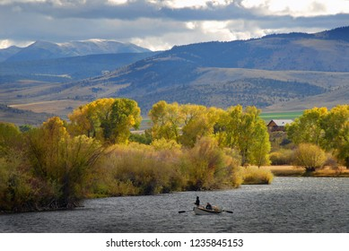 Anglers fly fishing the Madison River near Yellowstone National Park in Cameron Montana in autumn. Fall foliage lines the river banks while the Gravelly Mountains loom high.