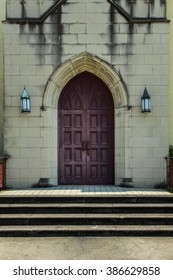 anglican-style church door flanked by sconces on yellow brick church