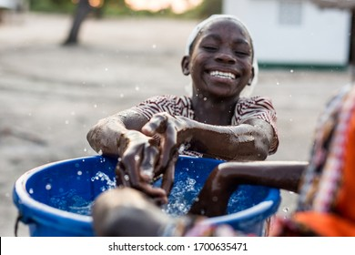 Angoche District, Nampula/ Mozambique - 11.20.2015: Young children play with water from a recently installed water well in a poor village in Northeast Mozambique.