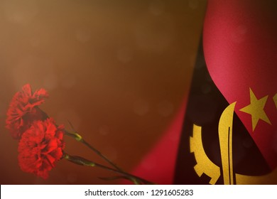 Angola flag with two red carnation flowers for honour of veterans or memorial day on orange dark velvet background. Angola glory to heroes of war concept.