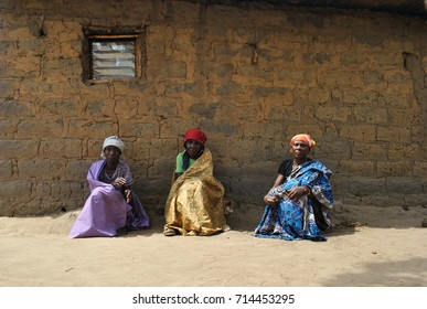 N´Dalatando, Angola, September 2013. Angolan women sitting in front of a house in a local village. Elderly people in developing countries. Cultural diversity. Traditional African dresses.