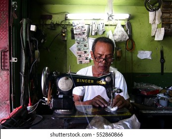 ANGONO, RIZAL, PHILIPPINES - DECEMBER 28, 2016: A sewing machine repair man tests a machine he fixed.