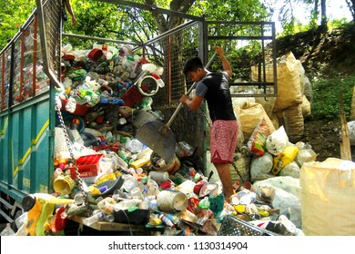 ANGONO, RIZAL, PHILIPPINES - JULY 4 2018: A worker at a materials recovery facility unload newly delivered plastic waste materials for sorting and segregation.