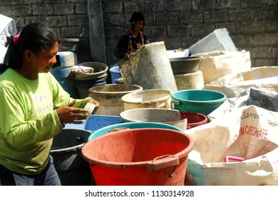 ANGONO, RIZAL, PHILIPPINES - JULY 4 2018: Workers of a materials recovery facility sort through plastic waste and segregate them for proper recycling.