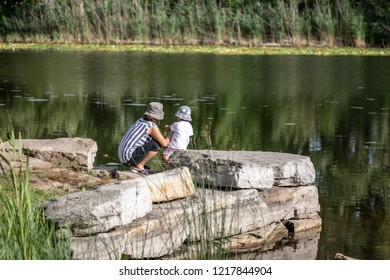 Angringnon Park, Lasalle, Quebec - August 31, 2018 - Sunny day in Angringnon Park, Lasalle with a mother and child on a rock face beside a lake with reflections