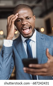 angry african american businessman screaming and using smartphone in cafe