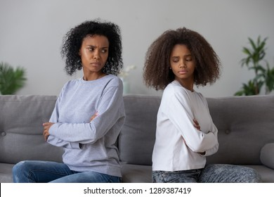 Angry African American mother and daughter sit back to back on couch, avoid talking or looking, mad black mom and teenage girl have fight or quarrel, stubborn parent and kid refuse to compromise