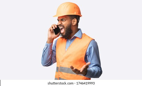 Angry African Builder Worker Yelling In Cellphone Standing In Studio On White Background. Panorama