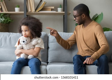Angry african father sitting with little stubborn daughter holds stuffed toy feels upset, dad scolds for discipline bad behaviour capricious kid, family generations problems, misunderstanding concept