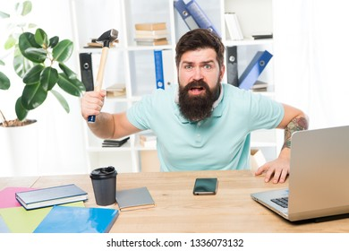 Angry aggressive businessman in office. Frustrated office worker holding hammer poised ready to smash. Office life makes him crazy. Businessman with beard and mustache gone mad with hammer in a hand.