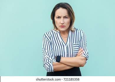 Angry, aggressive. Handsome elegant woman looking at camera with angry face . Studio shot, on light blue background.