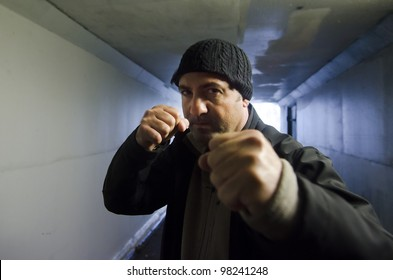 Angry aggressive violent mature adult man punching in a street fight inside a a city tunnel. Real people. copy space
