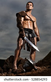 Angry ancient gladiator warrior posing on background dramatic landscape