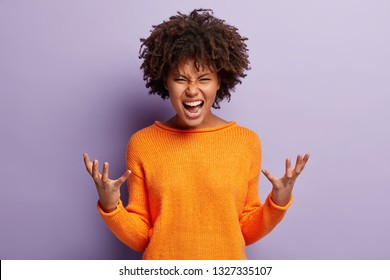 Angry annoyed female gestures with annoyance, screams loudly, expresses irritation, wears casual orange jumper, reproaches partner in betrayal, isolated over purple studio wall. Stop it please