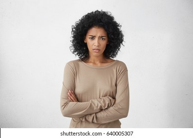 Angry annoyed young housewife keeping arms crossed and staring at camera with sceptical and distrustful look, feeling mad at someone. Human facial expressions, emotions and feelings. Body language