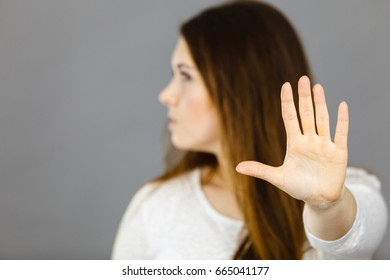 Angry apodicticity woman showing stop sign gesture with open hand, denying something,