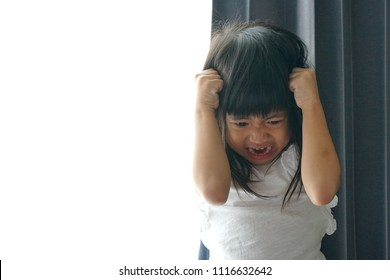 Angry Asian cute girl screaming, Copy space. Stressed child, Kid  with attention deficit hyperactivity disorder (ADHD) can't handle her emotion.