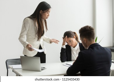 Angry asian executive shouting at subordinates scolding for bad results in report at diverse meeting, mad chinese female ceo boss leader dissatisfied with team incompetence reprimanding employees