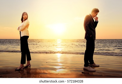 Angry Asian people woman and man turning their back on each other standing on sunset beach. Sad young couple in relationship difficulties. Broken heart or communication failure or divorce concept.
