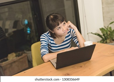 angry Asian young woman using laptop at home
