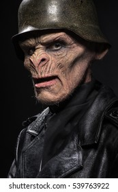 Angry baboonish man in black clothes on dark background