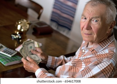 Angry and in a bad mood senior man counting and control finance from retirement, little savings, sitting at the table in the living room. Retirement, business, financial, wealth and success concept.