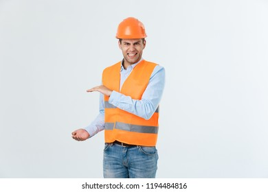 Angry beard engineer holding hand on side and explaining something, guy wearing caro shirt and jeans with yellow vest and orange helmet, isolated on white background