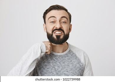 Angry bearded guy showing I will cut you head off gesture with index finger over neck, standing over gray background. I will hit you if you would not shut up now. Man is sick and tired of everything