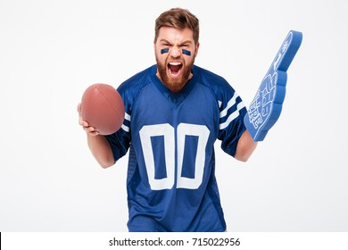 Angry bearded male fan screaming and cheering up isolated over white background. Holding rugby ball and fan finger
