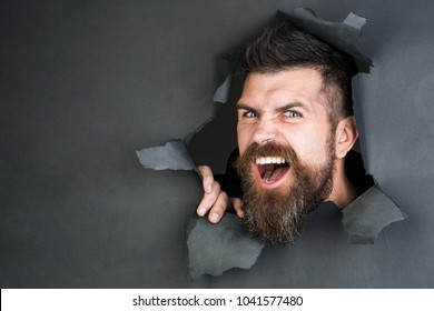 Angry bearded man making hole in paper. View of male face through hole in black paper. Bearded man looking through hole. Breaking paper.