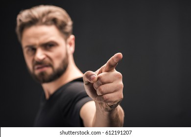 angry bearded man pointing  isolated on black with copy space