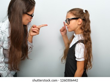 Angry beautiful woman in eye glasses scolding her pupil daughter and shwoung the finger on blue background