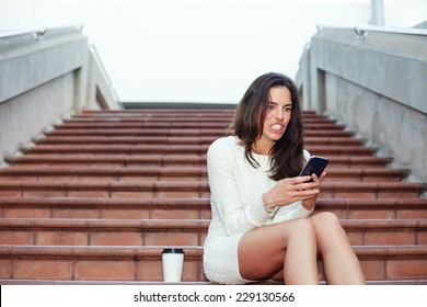 angry beautiful woman sitting on the stairs with mobile phone and cup of coffee