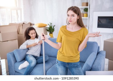 I am angry. Beautiful young girl cleaning the floor and being mad at her lazy roommate while she sitting texting on the sofa instead of helping her