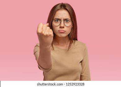 Angry beautiful young woman shows fist at camera, threats someone, being annoyed with noisy neighbours, purses lower lip, dressed in casual clothes, isolated over pink background, argues indoor