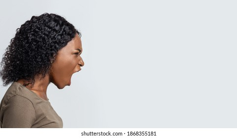 Angry black woman shouting towards copy space over grey background, panorama, side view. Furious african american lady screaming loud, saying about her problems or needs, expressing negative emotions