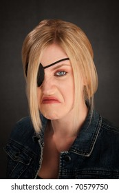 Angry blonde girl with eyepatch on grey background