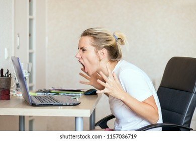 angry blonde woman working on laptop at home and screaming She's upset. Freelance, work at home concept