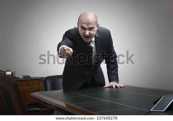 Angry boss behind of office table