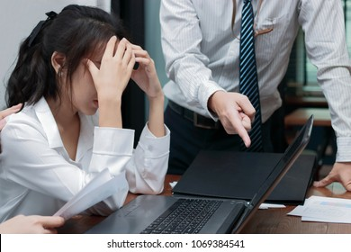 Angry boss blaming young Asian woman with hands on face in office.