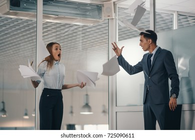 Angry boss fights aggressively with a subordinate or colleague in a suit. Throws all the paper documents on the floor and they fly apart.