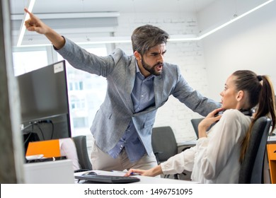 Angry boss firing upset female employee in office. Young male business manager yelling at scared and stressed business woman at her workplace.