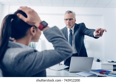 Angry boss outing his young office worker